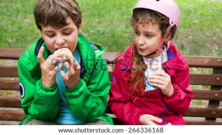 Boy and girl eating ice cream on a bench in park - stock photo