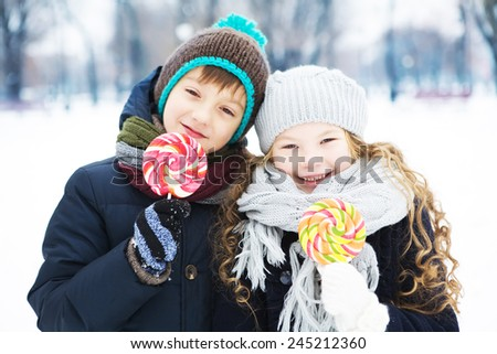 Boy and girl eating sweet candy in a winter park. Outdoor - stock photo
