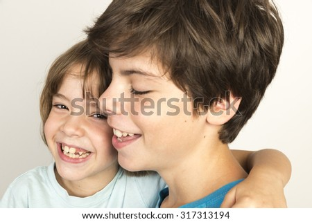 Boy and girl embracing and smiling at home isolated on white background - stock photo