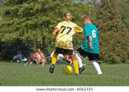 Boy and Girl Fight for Soccer Ball - stock photo
