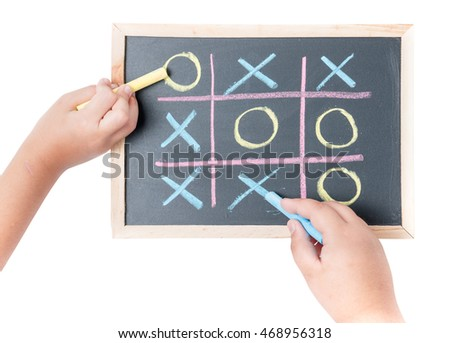 boy and girl hand drawing a game of tic tac toe on a black chalkboard isolated on white background
