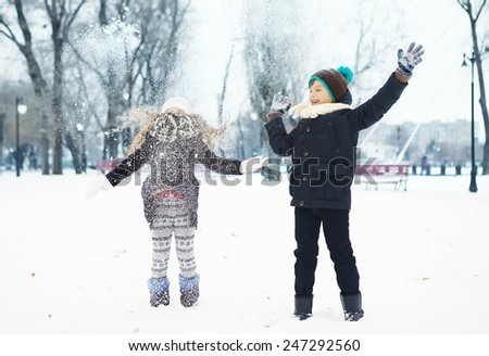boy and girl having fun in the park, jumping in the snow - stock photo