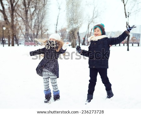 boy and girl having fun with the snow in winter park - stock photo
