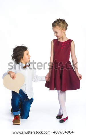 Boy and girl holding a cardboard heart. Love concept - stock photo