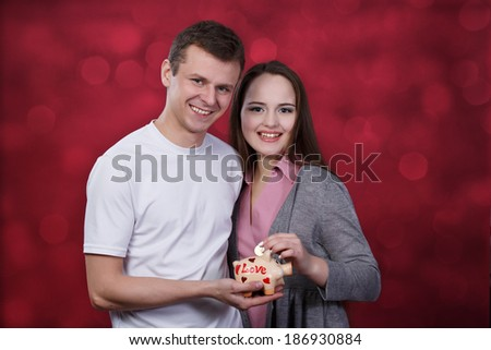 Boy and girl holding piggy bank at red background - stock photo