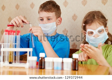 Boy and girl make chemical experiments, sitting at table - stock photo