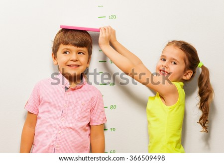 Boy and girl measure height by wall scale at home - stock photo