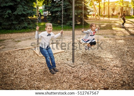 Boy and girl on a swing. Children playing outdoors in summer.