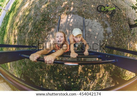 Boy and girl on outdoor playground hanging on the iron stairs. - stock photo