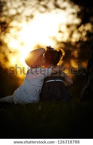 boy and girl on sunset - stock photo