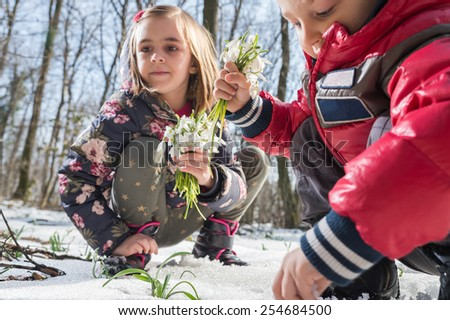Boy and girl picking flowers of spring - stock photo