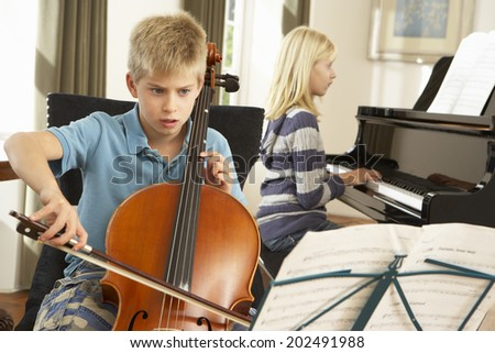 Boy and girl playing cello and piano at home - stock photo