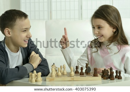 boy and  girl  playing chess - stock photo