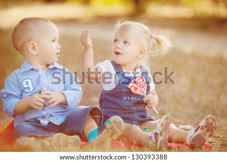 Boy and girl playing in summer park. Kids outdoor. - stock photo