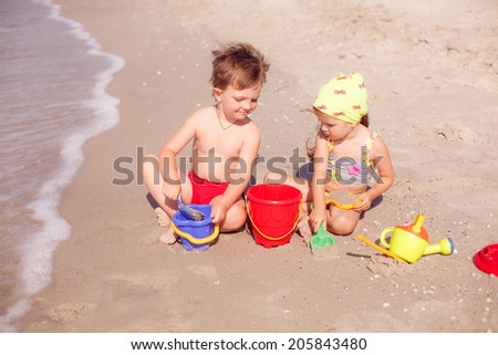 boy and girl playing in the sand on the seashore - stock photo