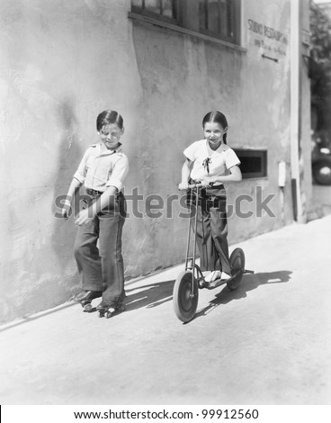 Boy and girl playing on a scooter and the other on roller blades - stock photo