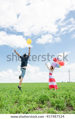boy and girl playing with balloons on the field