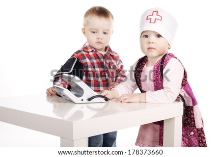 boy and girl playing with tonometer on white backround - stock photo