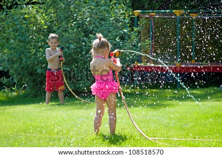 Boy and girl playing with water hoses in the garden - stock photo