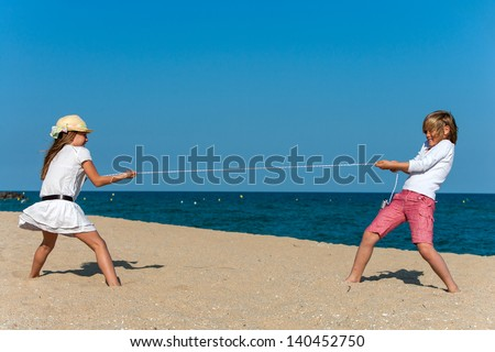 Boy and girl pulling the rope on the beach. - stock photo