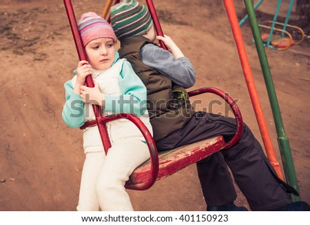 boy and girl riding on a swing back to back