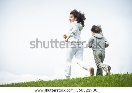 Boy and girl running and jumping on spring field in Alps - stock photo