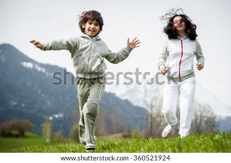 Boy and girl running and jumping on spring field in Alps