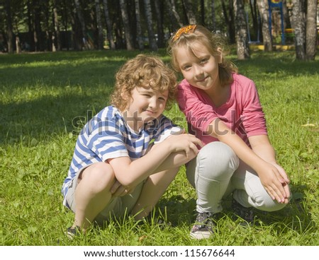 Boy and girl school age Caucasian sitting outdoors on grass near birch trees.