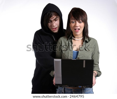 boy and girl searching the internet on a laptop - stock photo