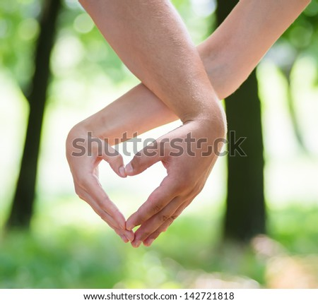 boy and girl shows a heart shape hands