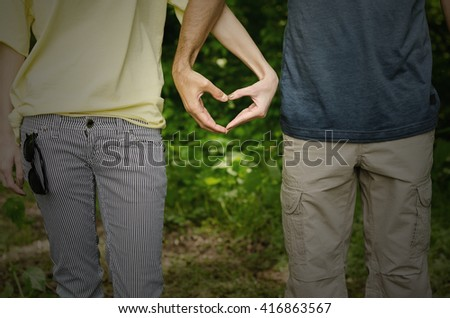 boy and girl shows heart by the hand of nature or the park