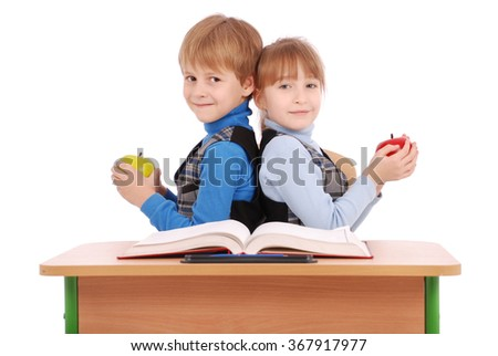 Boy and girl sit at a school desk and holding apple isolated on white