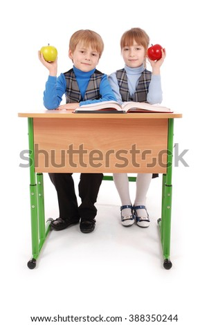 Boy and girl sit at a school desk and holding apple isolated on white - stock photo