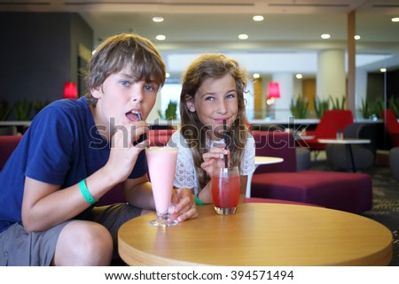 Boy and girl sit at a table and drink cocktails at the cafe, focus on girl - stock photo