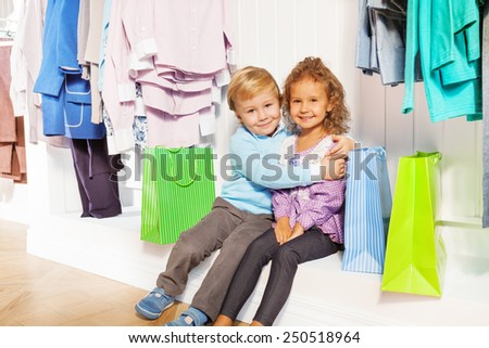 Boy and girl sit hugging under hangers in shop