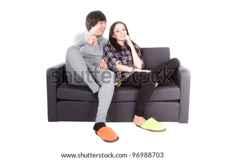 boy and girl sit on the sofa. They watch TV and discuss program