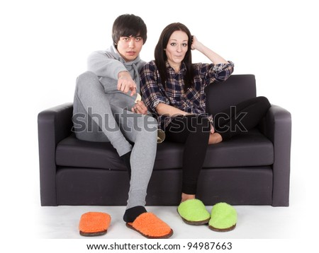 boy and girl sit on the sofa. They watch TV and discuss  programme