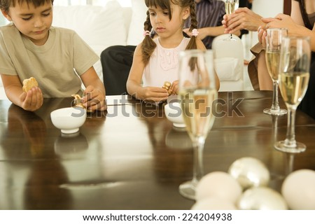 Boy and girl sitting at table, both holding Christmas ornaments, adults drinking champagne in background - stock photo