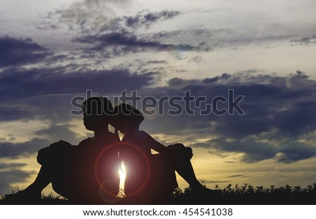 Boy and girl sitting on the sunset