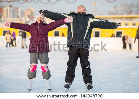 Boy and girl skating on rink and making hands to the side - stock photo