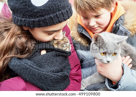 Boy and girl stand holding cats in arms.