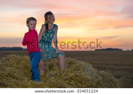 Boy and girl standing on a stack of straw yellow smiling on the background of the setting, the rising sun in the clouds - stock photo