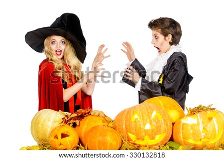 Boy and girl teenagers wearing halloween costumes posing with pumpkins. Isolated over white. Autumn holidays. - stock photo