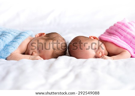 Boy and girl twins lying down in bed - stock photo