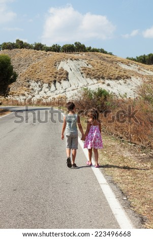 boy and girl walking along the street  - stock photo