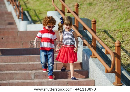 boy and girl walking on stairway - stock photo