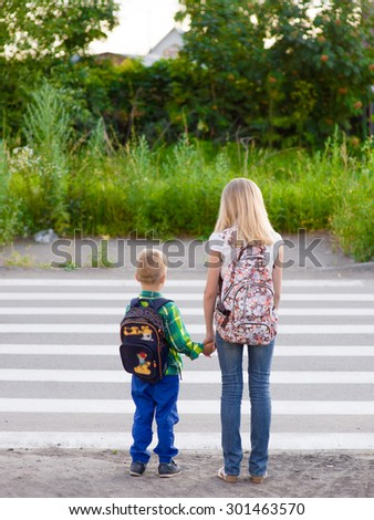 boy and girl want to cross the road at a pedestrian crossing - stock photo