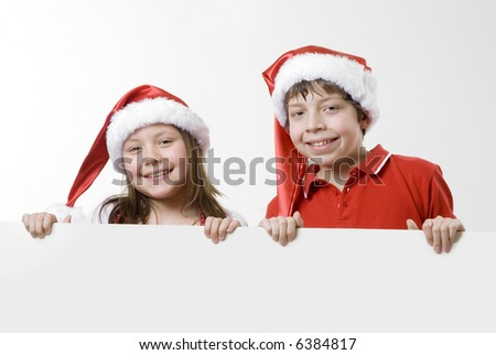 boy and girl wearing santa hats and red shirts holding a blank board