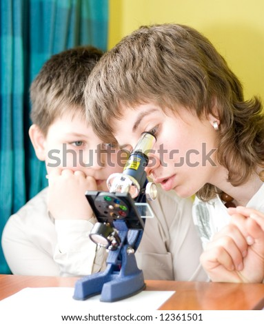 boy  and girl  with a microscope in a laboratory