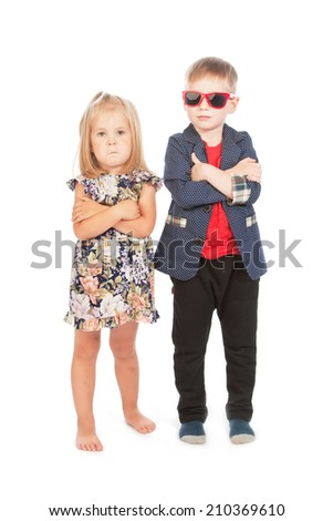 Boy and girl with arms across, studio portrait - stock photo